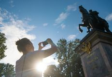 Woman taking pictures of Church. Woman photographs a monument to Peter the first in Saint-Petersburg royalty free stock photo