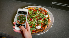 Woman photographs pizza at the phone Stock Images