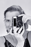 The woman photographs by a retro-camera. B&W Royalty Free Stock Photography