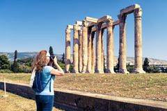 Woman photographs the Temple of Olympian Zeus, Athens. Young woman photographs the Temple of Olympian Zeus, Athens, Greece. It is one of the main tourist Royalty Free Stock Photography