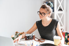 Woman photogtrapher drinking coffee and using laptop at the table. Attractive young woman photogtrapher in glasses drinking coffee and using laptop at the table Stock Photo