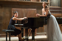 Woman pianist sits at the piano and beautiful singer