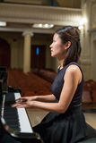 Woman pianist sits at the piano. In empty concert hall Stock Image