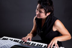 Woman with piano. Young woman with piano on gray background Stock Photos