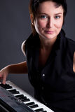 Woman with piano. Young woman with piano on gray background Royalty Free Stock Image