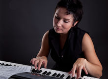 Woman with piano. Young woman with piano on gray background Royalty Free Stock Photo