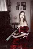 Woman and piano. Portrait of woman in old interior Royalty Free Stock Image