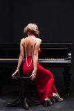 Woman and piano. Beautiful young attractive woman in cocktail dress and piano Stock Images