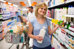 Woman picking bottle with shampoo from shelf in cosmetics sectio Royalty Free Stock Photography