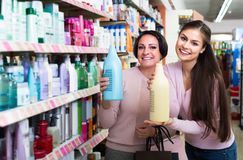 Woman picking bottles with shampoo and conditioner from shelf in Stock Photos