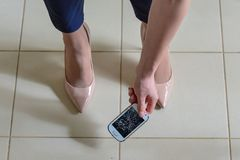 Woman picking broken smart phone with cracked screen of the tile. Floor stock images