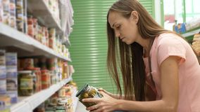 Woman picking canned food from the shelves at supermarket and reading the label. Young woman picking canned food from the shelves at supermarket and reading the Royalty Free Stock Photos