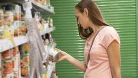 Woman picking canned food from the shelves at supermarket and reading the label. Young woman picking canned food from the shelves at supermarket and reading the Royalty Free Stock Photo