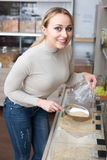 Woman picking cereals in organic store. Young woman standing next to jars with dried cereals and picking selected in organic store Stock Photos