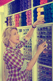 Woman picking cotton stitching spools. Mature glad woman customer picking various cotton stitching spools in sewing department Stock Photography