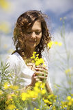 Woman picking flowers in rapeseed field. Stock Photos
