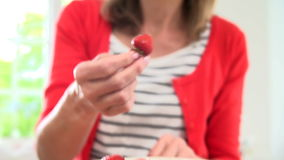 Woman Picking A Fresh Strawberry From Bowl And Eating Stock Photo