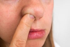 Woman is picking her nose with finger inside. Hygiene concept Royalty Free Stock Photos
