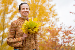 Woman Picking Leaves in Autumn Stock Images