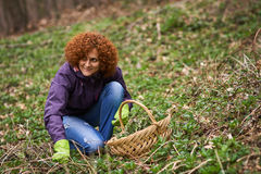 Woman picking nettles in a basket Stock Images