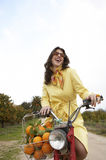 Woman Picking Oranges. Elegant young woman riding a motorbike in an orange grove stock photos