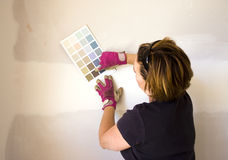 Woman picking paint for her wall Royalty Free Stock Image