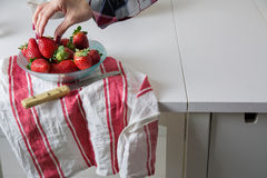 Woman picking strawberries a glass bowl Stock Images