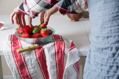 Woman picking strawberries a glass bowl Royalty Free Stock Photography