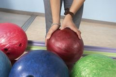 Woman Picking Up Bowling Ball Stock Photo