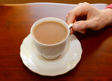 Woman picking up a cup of tea from a table royalty free stock photo