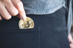 A woman picking up and dropping bitcoin into a black jean pocket. Closeup image of a woman picking up and dropping bitcoin into a black jean pocket Stock Image
