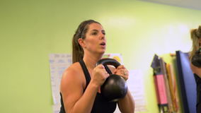 Woman picking up a kettle bell and working out stock footage