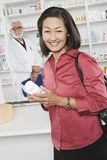 Woman Picking Up Prescription Drugs At Pharmacy Stock Image