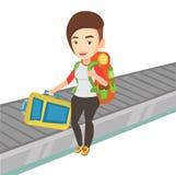 Woman picking up suitcase on luggage conveyor belt Stock Photos