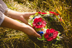 Woman picking up ukrainian wreath on wheat field Royalty Free Stock Photography