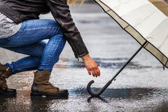 Free Woman Picking Up Umbrella From Puddle On Street In Rain Royalty Free Stock Photo - 184783895