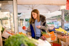 Woman picking vegetables at farmer`s market Royalty Free Stock Photos