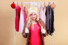 Woman picking winter outfit in wardrobe. Accessories and clothes for cold days, fashion concept. Blonde woman in winter warm furry hat and jacket, standing in Stock Image
