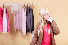 Woman picking winter outfit in wardrobe. Accessories and clothes for cold days, fashion concept. Blonde woman in winter warm furry hat and jacket, standing in Royalty Free Stock Photo