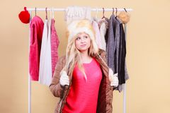 Woman picking winter outfit in wardrobe. Accessories and clothes for cold days, fashion concept. Blonde woman in winter warm furry hat and jacket, standing in Stock Images