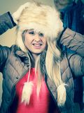 Woman picking winter outfit in wardrobe. Accessories and clothes for cold days, fashion concept. Blonde woman in winter warm furry hat and jacket, standing in Stock Photos