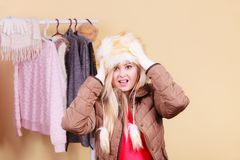 Woman picking winter outfit in wardrobe. Accessories and clothes for cold days, fashion concept. Blonde woman in winter warm furry hat and jacket, standing in Royalty Free Stock Image