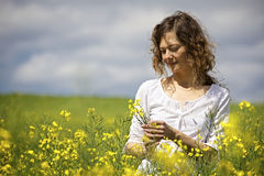 Woman picking yellow flowers in field. Royalty Free Stock Images