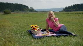 Woman picks a berry while lying on the blanket during picnic. Young blonde female picks grape berries while laying on the blue blanket stock footage