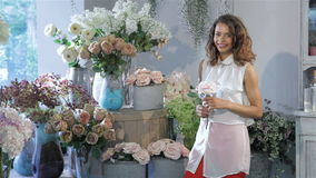 Woman picks one rose from the vase at flower shop stock video footage