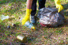 Woman picks up garbage. In a forest park area Royalty Free Stock Photo