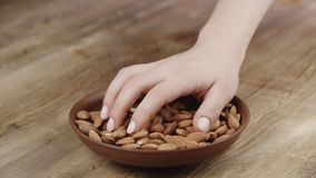 Woman picks up a handful of almonds, to eat, from her bowl. Took a nut on the right side. 4k stock footage