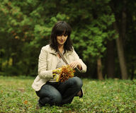 Woman picks up leaves Stock Images