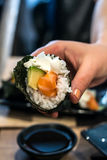 Woman picks up Temaki sushi roll with fresh salmon, avocado and philadelphia cheese Royalty Free Stock Image