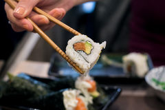 Woman picks up Uramaki sushi roll with fresh salmon, avocado and philadelphia cheese, covered with sesame seeds Royalty Free Stock Photo